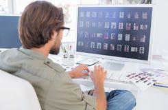 Editor de fotos que mira uñas del pulgar en el ordenador imagen de archivo libre de regalías