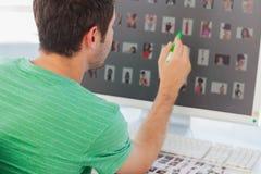 Editor de fotos que señala en su pantalla con un marcador verde foto de archivo