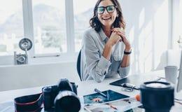 Editor de fotos de sexo femenino que se sienta en su escritorio fotos de archivo