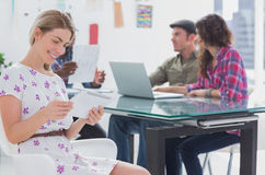 Editor holding tablet and smiling as her team works behind her Royalty Free Stock Photos