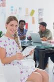 Editor holding tablet and smiling at camera as her team works be Stock Image