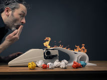 Editor with hot story. Surprised editor with his typewriter and flames on his written story stock image