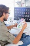 Editor looking at colour wheel Royalty Free Stock Photos