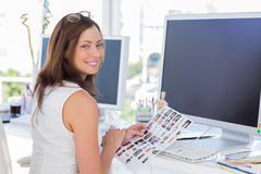 Editor looking over shoulder at camera at her desk. And smiling Stock Image