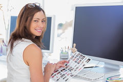 Editor looking over shoulder at camera. And smiling Stock Photo