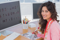 Editor marking the contact sheet and smiling at camera Stock Images