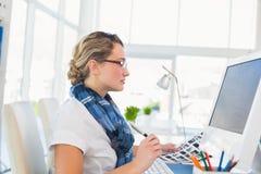 Editor novo focalizado que trabalha em sua mesa Imagem de Stock