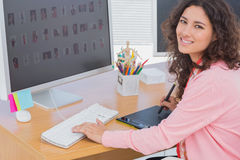 Editor using graphics tablet to do work and smiling at camera Royalty Free Stock Photography