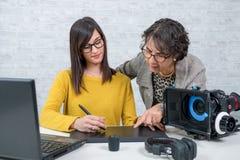Editor video da mulher e assistente novo que usa a tabuleta gráfica Imagens de Stock Royalty Free