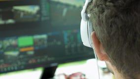 Editor video da transmissão com os fones de ouvido contra a tela filme
