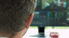 Editor video da transmissão com os fones de ouvido contra a tela vídeos de arquivo