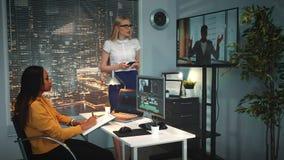 Editor video profissional que analisa o projeto video com o colega no estúdio da produção filme