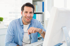 Editor working at his computer while looking at camera Stock Photos