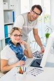 Editores de fotos de sorriso que usam o computador Fotografia de Stock