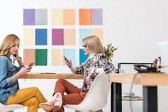 editores de revistas elegantes que trabalham com os smartphones no local de trabalho com paleta de cores fotografia de stock royalty free
