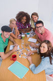 Editores que olham acima na câmera em uma reunião Fotografia de Stock Royalty Free