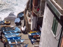 Editorial boats on pavement waterfront Riomaggiore, Cinque Terre, Italy royalty free stock photos