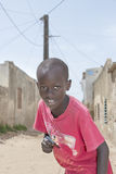 Editorial caption: THIAROYE, SENEGAL, AFRICA – JULY 30, 2014 – Unidentified boy standing in the street Stock Photos