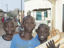 Editorial caption: Thiaroye, Senegal, Africa – July 28, 2014: Unidentified children (bread delivery boys) in the street Royalty Free Stock Photography