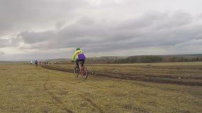 editorial Cavaleiros novos da bicicleta que movem-se no campo em video estoque