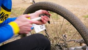 EDITORIAL. Contesting Cyclist Pumping In The Tire stock footage
