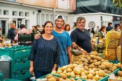 Editorial ilustrativo da família amigável de vendedores do mercado no mercado do alimento do ` s de Cascais Foto de Stock