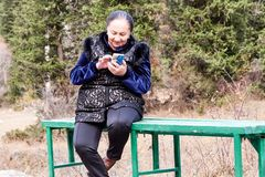 Age is not a hindrance to technology. Editorial,Kyrgyzstan, Bishkek, Ala-Archa gorge 10/06/2018,Asian grandmother sits on a bench, playing in the phone in the royalty free stock images