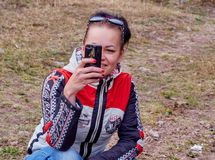 Girl takes pictures on the phone royalty free stock photography
