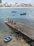 Editorial men are seen on pier Las Canteras Beach with hotels in Royalty Free Stock Image