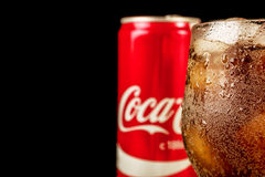 Editorial photo of Close-up Coca-Cola glass with ice and can on wooden table and copy space on black. Horizontal photo. MINSK, BELARUS - JUNE 20, 2017: Close-up Stock Photos