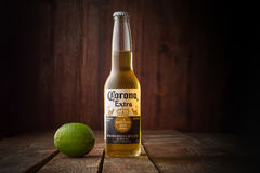 Editorial photo of Corona beer with lime on dark wooden background with copy space. MINSK, BELARUS - APRIL 3, 2017: Editorial photo of bottle of Corona Extra stock photos