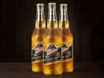 Editorial photo of Miller Genue Draft Beer bottles on dark wooden background Royalty Free Stock Photography