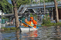 Editorial photo of two Buddhist monks floating in a boat on a flooded street in Bangkok in 2011 Stock Images