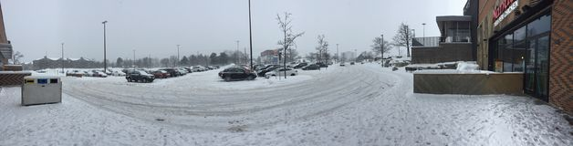 Editorial photo of a very snowy parking lot at shopping mall after snow storm. Panorama photograph of a parking lot after a snow storm in Canada. Parking lots Royalty Free Stock Images