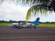 Editorial tourist leaving plane Corn Island Airport Nicaragua. BIG CORN ISLAND, NICARAGUA-AUG. 27: Tourists disembarking from twin prop La Costena Airline plane Stock Images