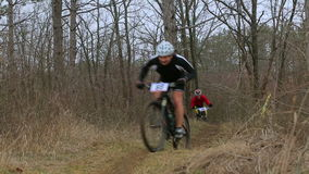 EDITORIAL. Two Mountain Bikers Racing In Forest
