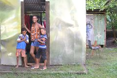 Editorial woman boys zinc house Corn Island Nicaragua. CORN ISLAND, NICARAGUA-NOVEMBER 16: A woman and two native Creole boys stand proudly in front of newly stock photos