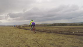 EDITORIAL. Young Bicycle Riders Moving In Field At stock video