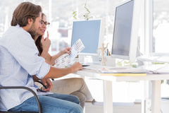 Editors going over the contact sheet. At their desk in office Stock Photography