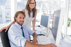 Editors smiling at the camera. At their desk in modern office Stock Photography