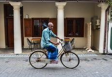 Edlerly um homem que conduz uma bicicleta em ruas fotos de stock