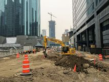 A large construction site in downtown Edmonton, Alberta with an excavator and construction workers continuing work. Edmonton, Alberta, Canada - May 30th, 2019: A stock image