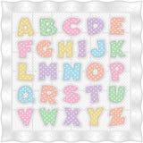 Edredón blanco del bebé con alfabeto en colores pastel del punto de polca Fotografía de archivo