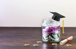 A educação é etiquetada no frasco de vidro completamente das moedas fotos de stock royalty free