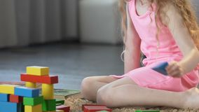 Educação adiantada, criança fêmea esperta que joga com blocos do brinquedo em casa, infância vídeos de arquivo