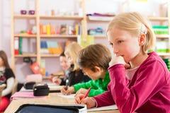 Educação - alunos na escola que faz trabalhos de casa Imagens de Stock Royalty Free