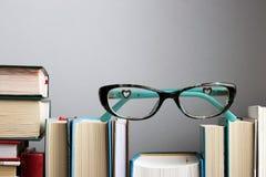 Educação Conceito da leitura e da escrita Monóculos à moda na estante foto de stock