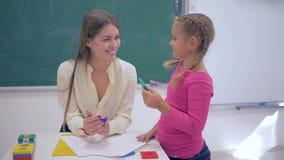 Educação das crianças, tutor novo que usa figuras plásticas para ensinar a estudante esperta na tabela perto da placa na sala de  video estoque