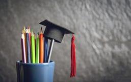 Educação e de volta ao conceito da escola com o tampão da graduação na cor dos lápis em uma caixa de lápis no fundo escuro imagens de stock