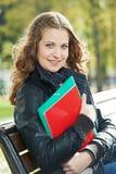 Educação e estudo Estudante fêmea feliz Menina com livros de nota e manuais de instruções no parque fora Foto de Stock